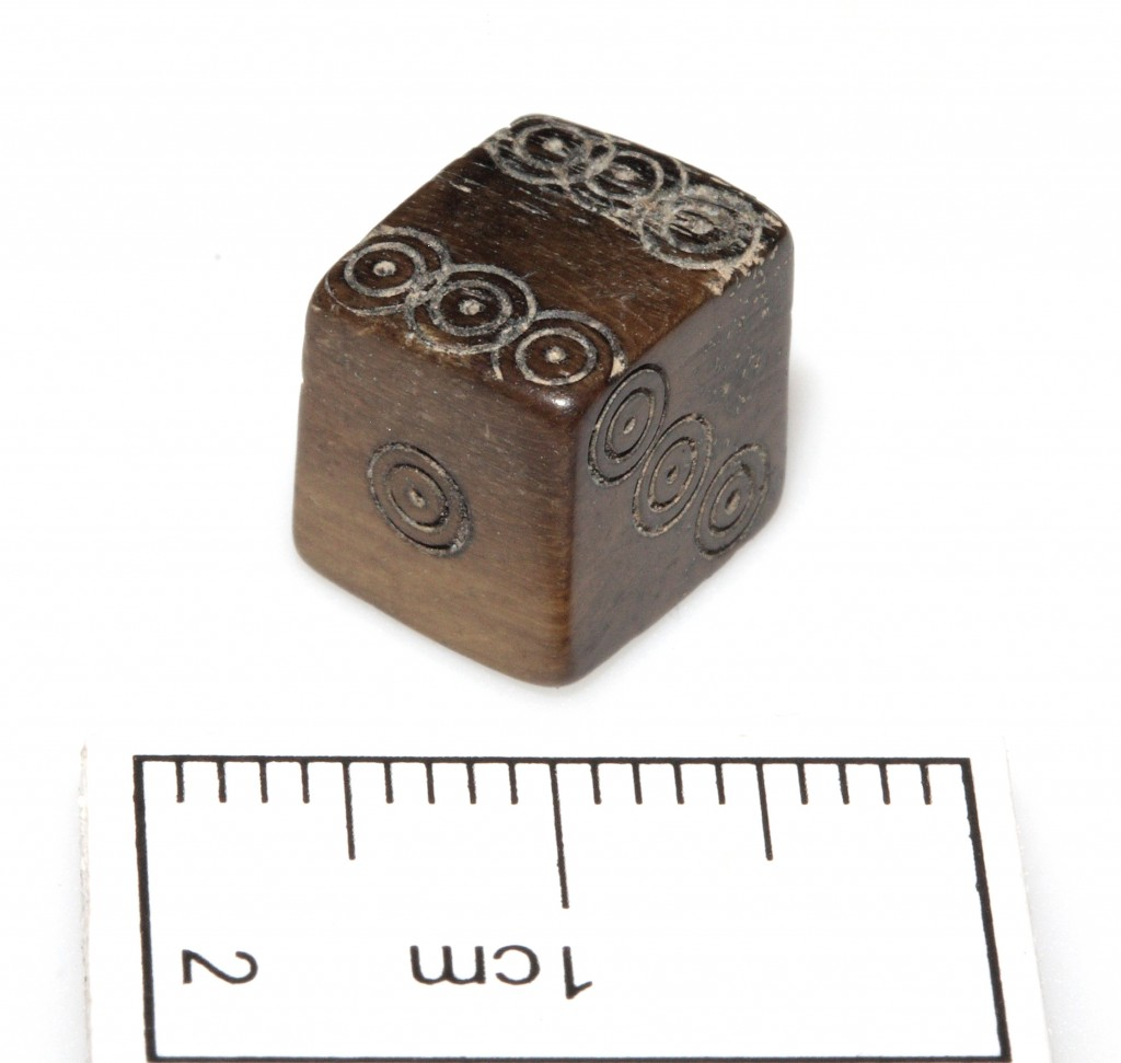 Medieval die with scale, showing the tiny size of this exquisite object