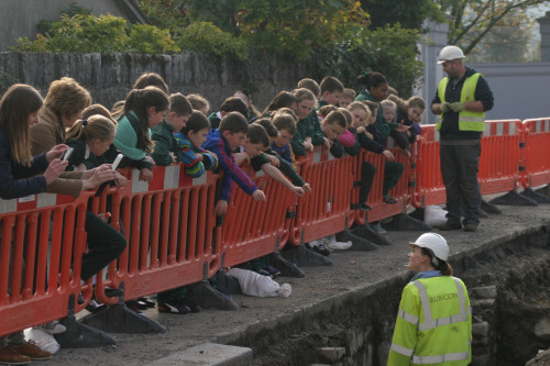 Students from 4th Class of Buttevant Primary School viewed the site with their teacher Mary Linehan and teaching assistant Cora Nash. Here archaeologists Liza and Dave show them the remains of the cellar (Copyright Rubicon Heritage)